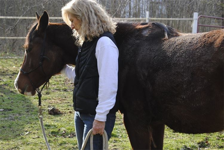 Woman standing next to a horse