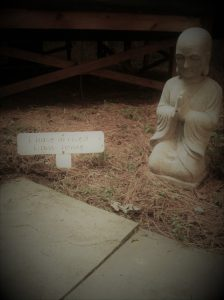Statue of a monk praying next to a sign
